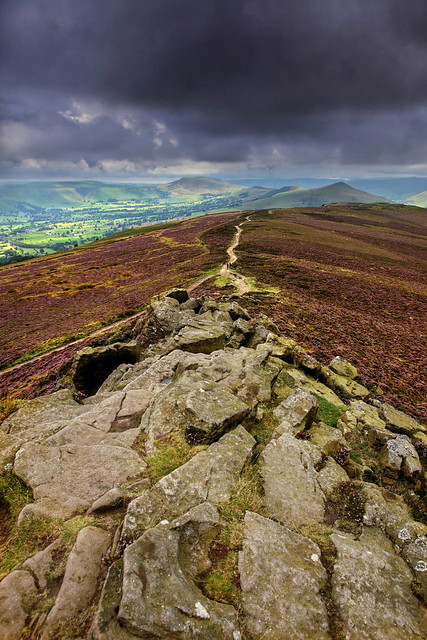 A photo from the peak of win hill over the valley and mam tor, lose hill and the ridge. All under stormy weather.