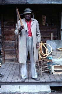 Alvin Goodvine standing on his front porch holding whips: Lake City, Florida