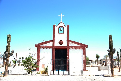 Rural Mexican church, white with red trim, adobe, bell, arch, cross, white sand, Saguaro cactus, graveyard, blue sky, Baja California Sur, Mexico by Wonderlane