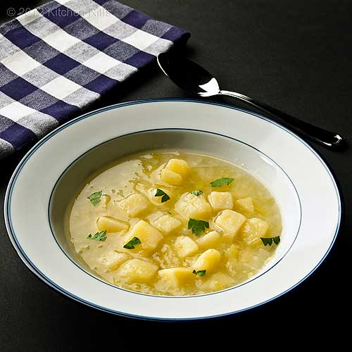 Leek and Potato Soup in Bowl with Napkin and Spoon, Black Background