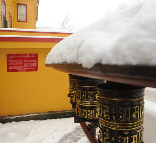 Tibetan Buddhist prayer wheels in the snow, bright yellow-orange paint, Parinirvana Stupa and Pray Wheels, Sakya Monastery of Tibetan Buddhism, Seattle, Washington, USA by Wonderlane
