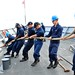 Sailors heave a mooring line.