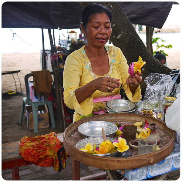 Balinese woman crafting flower offerings
