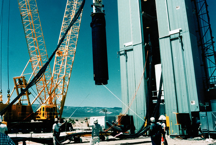 "The ""Divider"" test rack is hoisted into position for lowering down hole at the Nevada Test Site in September of 1992.  Divider was the last full scale underground nuclear test conduced by the United States."