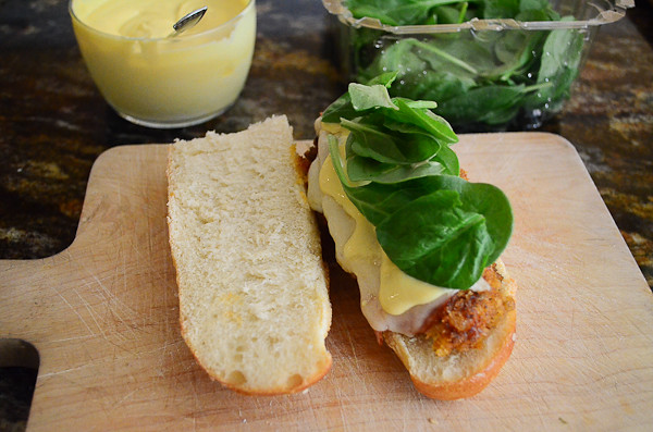 Several leaves of baby spinach are added on top of the sandwich.