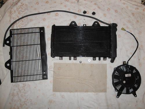 Wider radiator with fan, plastic stone guard and aluminium grill