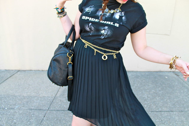 Black and gold outfit: Vintage Spice Girls t-shirt, high-low-hem pleated sheer skirt, Dior letter charm chain belt, jeweled leopard sandals, studded-bottom bag, studded friendship bracelet, etc.