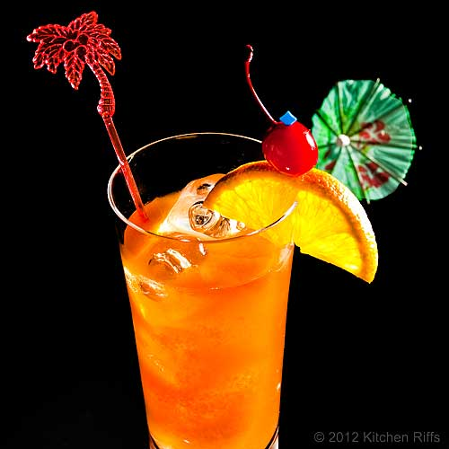 Bermuda Rum Swizzle with Swizzle Stick, Orange Slice, and Maraschino Cherry Garnish, Black Background