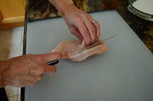 The top of the chicken breast being pulled back while a knife cuts through the center.