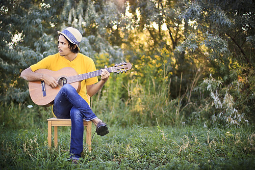Joshua James with guitar in field