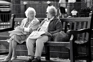 An elderly couple taking time out for a snack and watching passers by