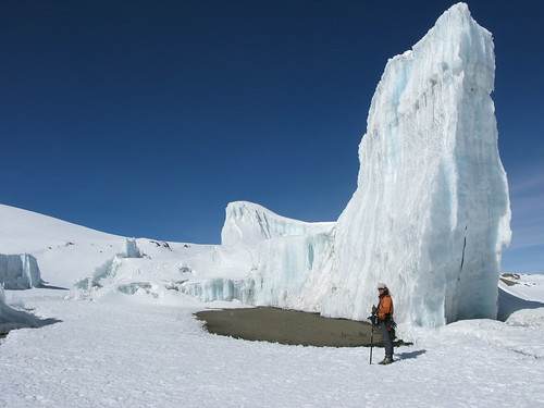 A team member stands by a glacier