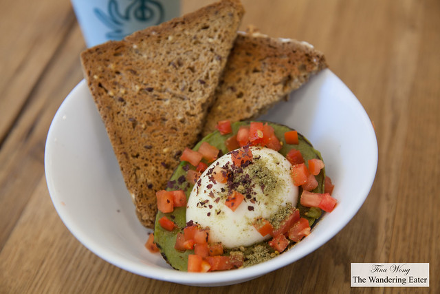Avocado Baked Egg topped with chopped tomatoes, seaweed flakes and spices