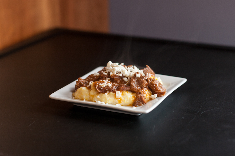 Beef tongue with tomatoes served on creamy polenta and topped with freshly crumbled cotija cheese