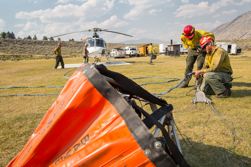 Helitack crew members rig a helicopter for bucket drops