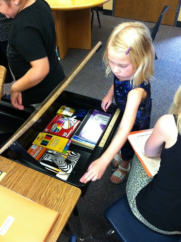 The third grader arranges her desk (for the first time of three).