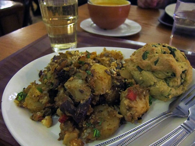 A plateful of cauliflower, potatoes, and other veggies with a scone. In the background is a bowl of soup.