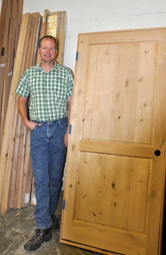 "Having weathered tough economic times, Pacific Pine Products, Inc. is on track to have a record year for 2012, hammering out roughly 5,000 doors each month. ""I can't believe there are so many people buying doors,"" says company vice president Greg Larson (shown with product)."
