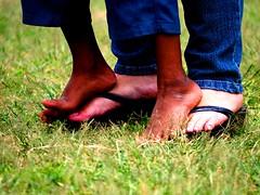 hand(0.0), shoe(0.0), human body(0.0), footwear(1.0), grass(1.0), barefoot(1.0), limb(1.0), green(1.0), leg(1.0), meadow(1.0),