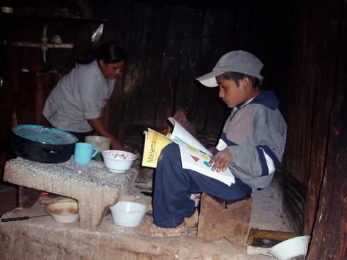 Gilberto estudiando por la fogata, y su madre Ester haciendo comida - Gilbert studying by the fire, while his mother cooks food; Monte Negro, Región Mixteca, Oaxaca, Mexico