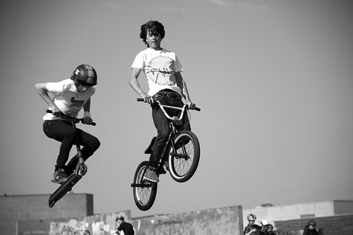 Mountain bike and skateboarder in action