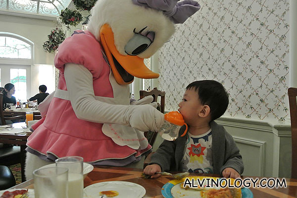 Daisy Duck feeding water to Asher