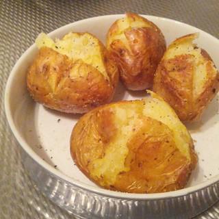 4 gepofte aardappels met een kruis in het midden gesneden en wat samengedrukt zodat je de aardappel in de schil kan zien zitten. Er zitten vlekjes van het peper en zout op de aardappels en de schil is gerimpeld en glimt een beetje. De aardappelen zitten in een kleine taartschaal die grijs is van buiten en wit van binnen. Het oppervlak waar hij op staat is van metaal en geribbeld.