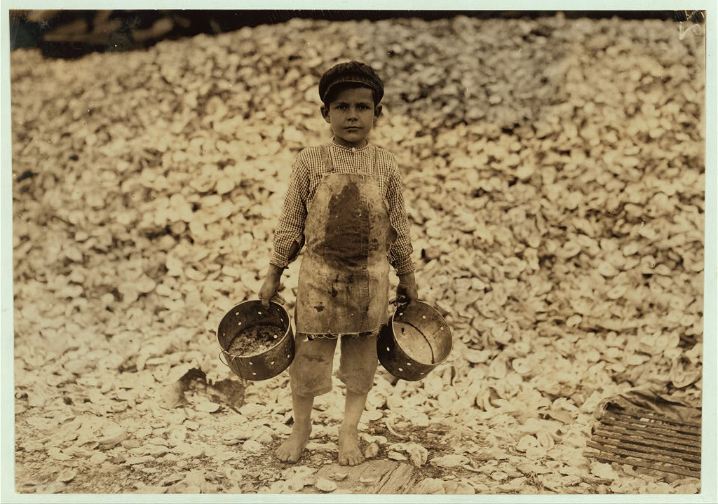 Manuel, the young shrimp-picker, five years old, and a mountain of child-labor oyster shells behind him. He worked last year. Understands not a word of English. Dunbar, Lopez, Dukate Company.  Location: Biloxi, Mississippi.