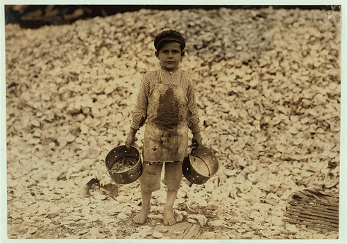 Manuel, the young shrimp-picker, five years old, and a mountain of child-labor oyster shells behind him. He worked last year. Understands not a word of English. Dunbar, Lopez, Dukate Company.  (LOC)