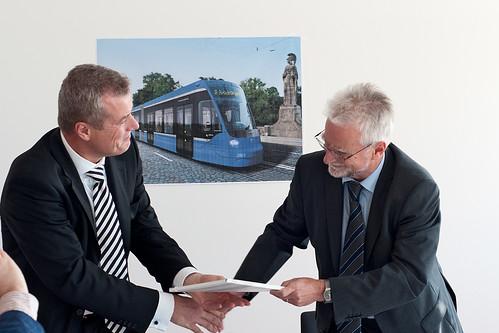 MVG-Chef Herbert König (re.) überreicht die Mappe mit der Avenio-Bestellung an Dr. Jochen Eickholt (Siemens Rail Systems)