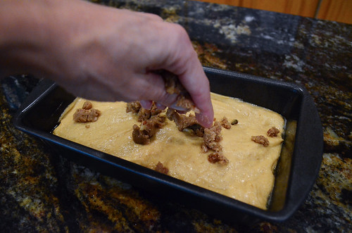 Streusel topping being sprinkled on top of the batter.