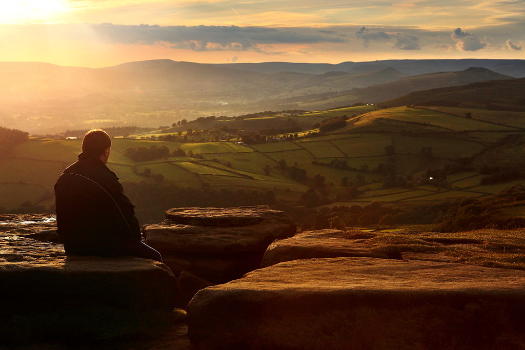 Warm light silhouette of a man looking over a vast peak district landscape