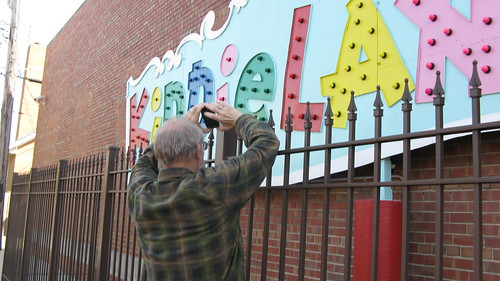 Mike Mikrut photographs the preserved portion of the old Kiddieland Amusement Park sign at the Melrose Park Public Library building. by Eddie from Chicago