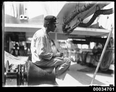 Japanese sailor sitting on a winch probably on board naval vessel TAISEI MARU, 1906-1934