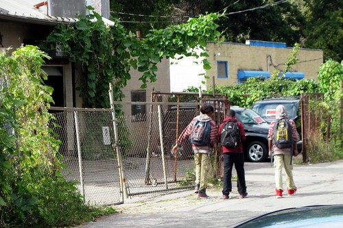 kids walk home from school past deteriorated commercial buildings (c2012 FK Benfield)