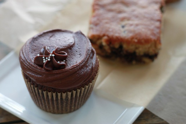 Close-up of the chocolate cupcake. It has a small frosting flower on top.