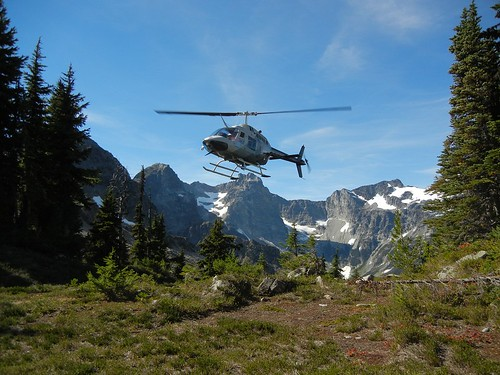Snow survey team arrives by helicopter to repair site.