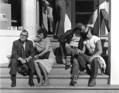A still photo from We Were Here of a gay couple kissing next to a straight couple who are avoiding looking at them.