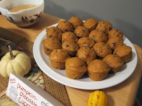 Close-up of a plate full of mini pumpkin chocolate-chip muffins. In the background is a bowl full of a creamy pumpkin-cream cheese dip.