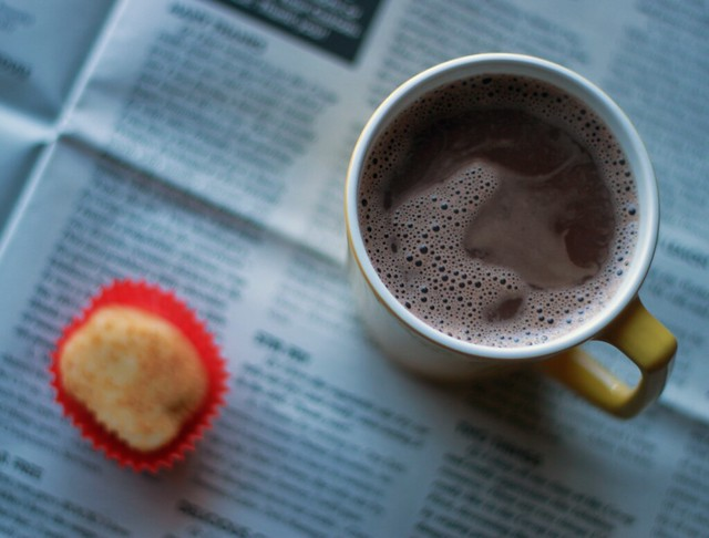 Top-down view of a yellow mug filled with hot chocolate and a single piece of mochi sitting in its red wrapper. Both items are on an open newspaper.