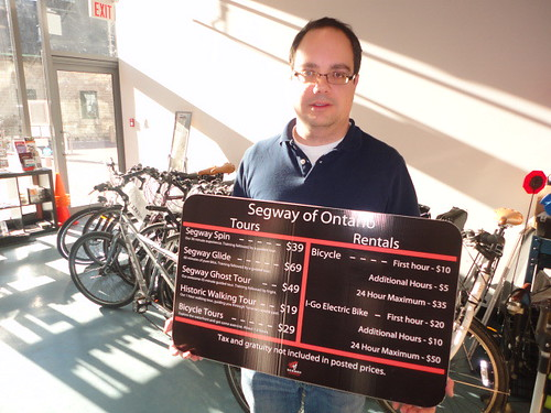 Jason Rizzuti holds a sign advertising walking tours on Segway with prices, fees