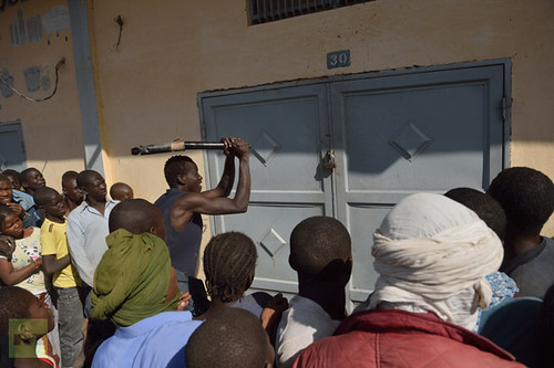 A Malian tries to break the lock off a store front as looters and residents stand by in the streets of Timbuktu on January 29, 2013. by Pan-African News Wire File Photos
