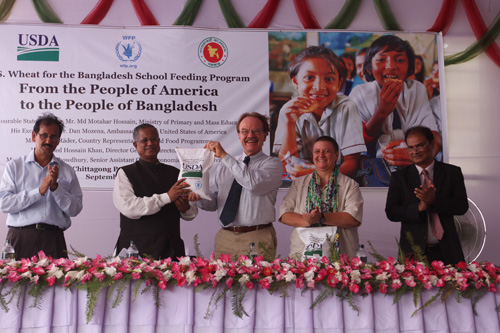 United States Ambassador to Bangladesh Dan W. Mozena (center) hands over a ceremonial bag of wheat to Bangladesh's State Minister for Primary and Mass Education Md Motahar Hossain during a ceremony at a Bangladeshi port last month. The event marked the donation of more than 10,000 metric tons of wheat to the country through the Foreign Agricultural Service's (FAS) McGovern-Dole Food for Education Program. The wheat will be used to provide approximately 350,000 Bangladeshi school children with a nutritious snack. (Photo courtesy U.S. Embassy New Dehli)
