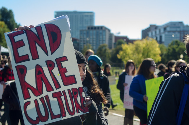 "A protester holds a sign saying ""end rape culture."""