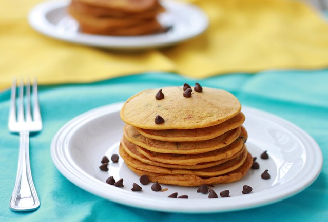 Bright blue cloth with a white plate and a stack of seven thin, orange pumpkin pancakes. Scattered around them are a few mini chocolate chips.
