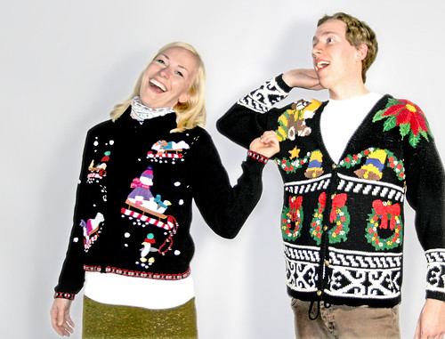 Man and woman smiling, wearing ugly Christmas sweaters.