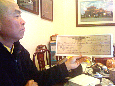 Abbot Thich Quang Thanh with an enlarged copy of a check that went into the Vietnamese Interfaith Council account instead of Hurricane Sandy aid fund.