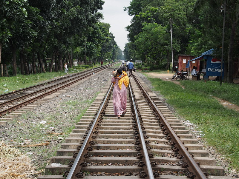 A mother and a child walking on railway track