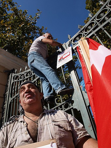 Greek protester climbing gates to ministry building to hang banner by Teacher Dude's BBQ