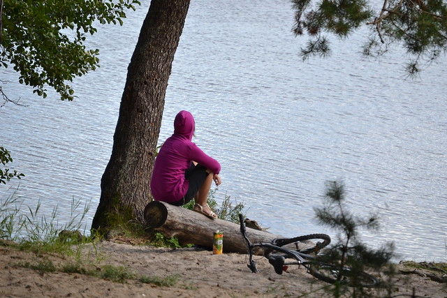 mujer sentada sobre un tronco el parque pensando, al lado de una bicicleta